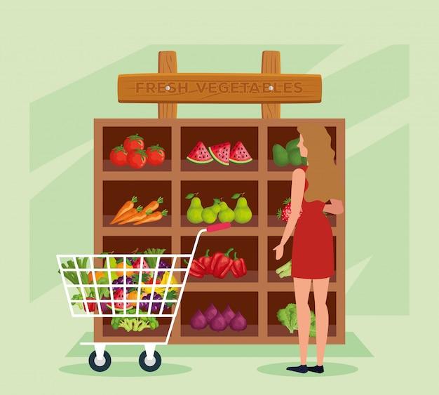 Mujer cliente en la tienda natural con verduras y frutas.