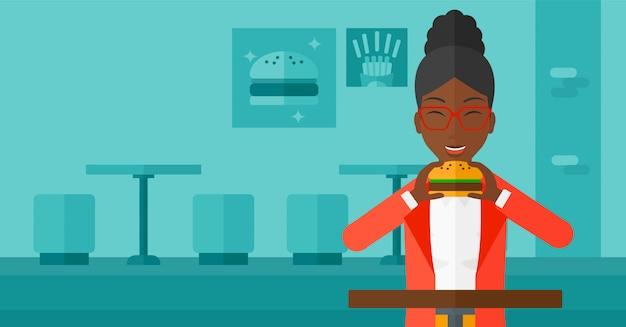 Mujer comiendo hamburguesa.