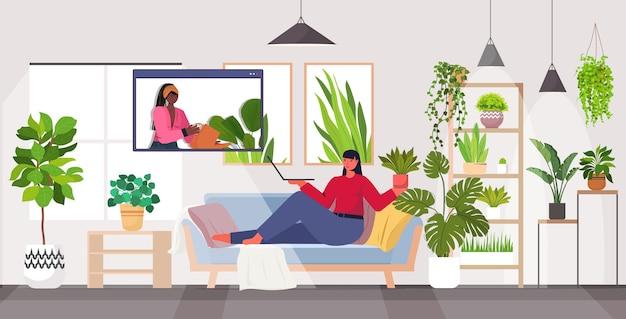 Mujer cuidando de ama de casa de plantas de interior discutiendo con un amigo en la ventana del navegador web durante la videollamada horizontal
