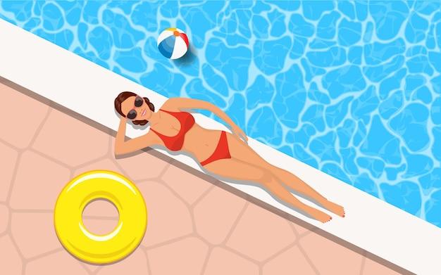 Mujer delgada en bikini relajante junto a la piscina.