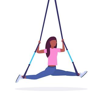 Mujer deportiva haciendo ejercicios de división con correas de fitness de suspensión cuerda elástica chica entrenamiento en gimnasio crossfit cardio entrenamiento concepto fondo blanco longitud completa