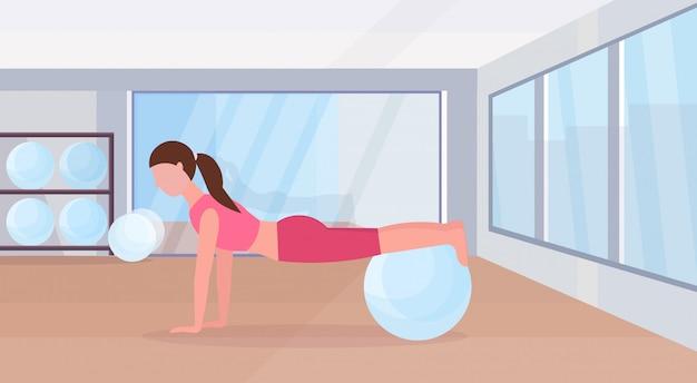 Mujer deportiva haciendo ejercicios con fitness ball entrenamiento de la niña en el gimnasio aeróbico pilates entrenamiento estilo de vida saludable concepto plano moderno club de salud studio interior horizontal