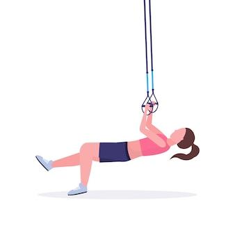 Mujer deportiva haciendo ejercicios con suspensión correas de fitness cuerda elástica chica entrenamiento en gimnasio crossfit cardio entrenamiento estilo de vida saludable concepto fondo blanco longitud completa