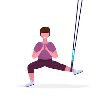 Mujer deportiva haciendo sentadillas ejercicios con suspensión correas de fitness cuerda elástica chica entrenamiento en gimnasio crossfit cardio entrenamiento estilo de vida saludable concepto fondo blanco longitud completa