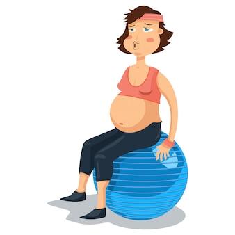 Mujer embarazada en la pelota de gimnasia