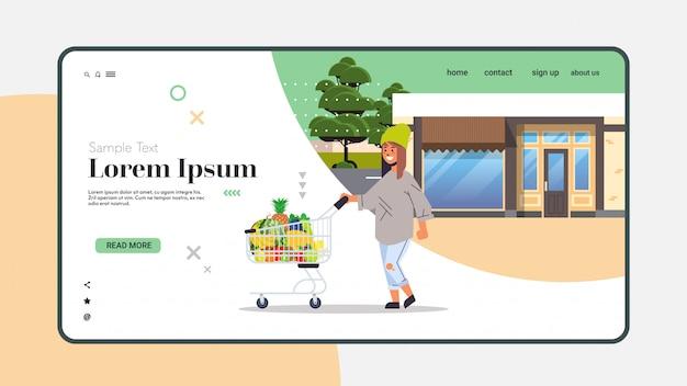 Mujer empujando el carrito con diferentes frutas tropicales dulces estilo de vida saludable concepto de comida vegana horizontal copia espacio integral