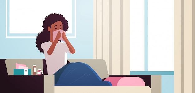 Mujer enferma sonarse la nariz con el pañuelo chica afroamericana insalubre limpieza nariz mocosa tener estornudos de gripe sentado en el sofá enfermedad concepto moderno salón interior retrato horizontal