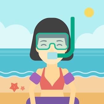 Mujer con equipo de snorkel en la playa.