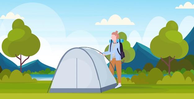 Mujer excursionista camper instalando una carpa preparándose para acampar excursionista viajero concepto en caminata hermosa naturaleza paisaje fondo plano horizontal de longitud completa