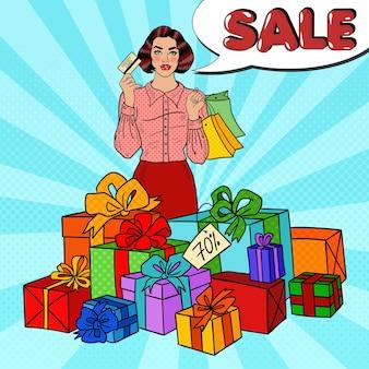Mujer feliz de arte pop con bolsas de compras, enormes cajas de regalo y venta de burbujas de discurso cómico.