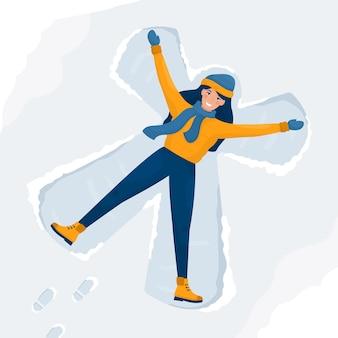 Mujer feliz hace ángeles de nieve y tirado en el suelo