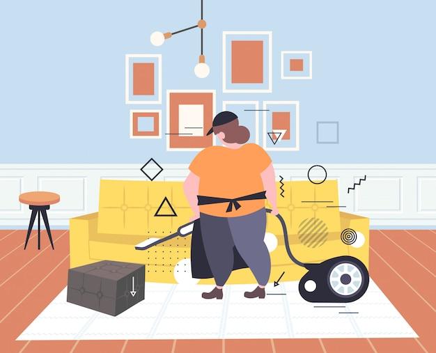 Mujer gorda que usa la aspiradora conserje femenino en el sofá de aspiración uniforme haciendo tareas domésticas servicio de limpieza concepto moderno salón interior horizontal boceto integral