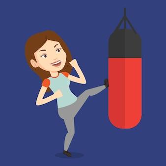 Mujer haciendo ejercicio con saco de boxeo.