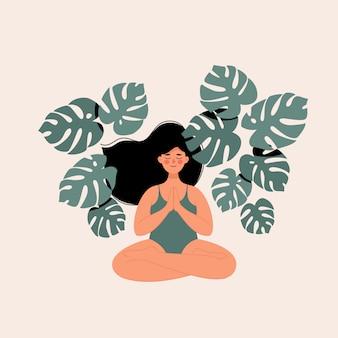 Mujer haciendo yoga en posición de loto rodeado de hojas de monstera