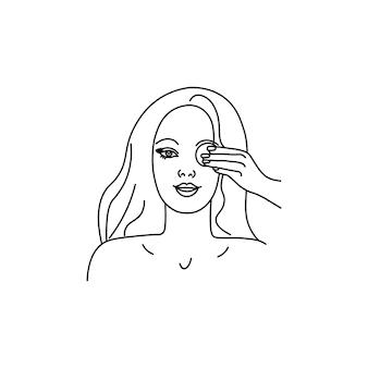 Mujer hermosa joven se limpia la cara con una esponja desmaquillante