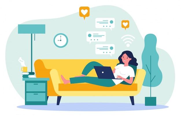 Mujer hermosa que se relaja en el sofá con la computadora portátil