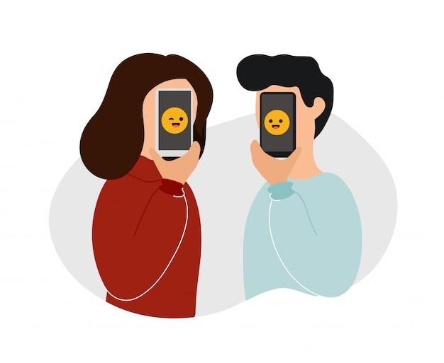 Mujer y hombre cubriendo rostros con teléfonos con emojis