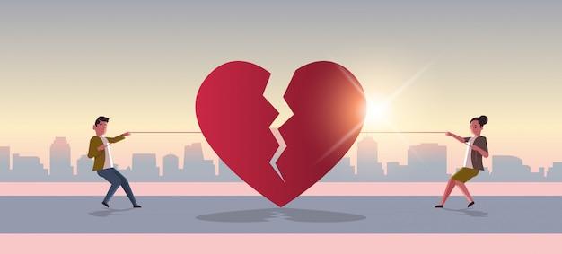 Mujer hombre tirando de la cuerda rasgando rojo corazón roto