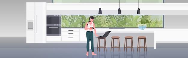 Mujer independiente bebiendo café trabajando en la computadora portátil quedarse en casa coronavirus pandemia concepto de cuarentena