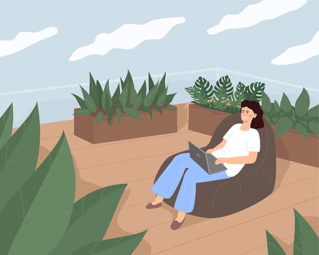 Una mujer joven y bonita está trabajando o relajándose sentada en una acogedora bolsa en la terraza.
