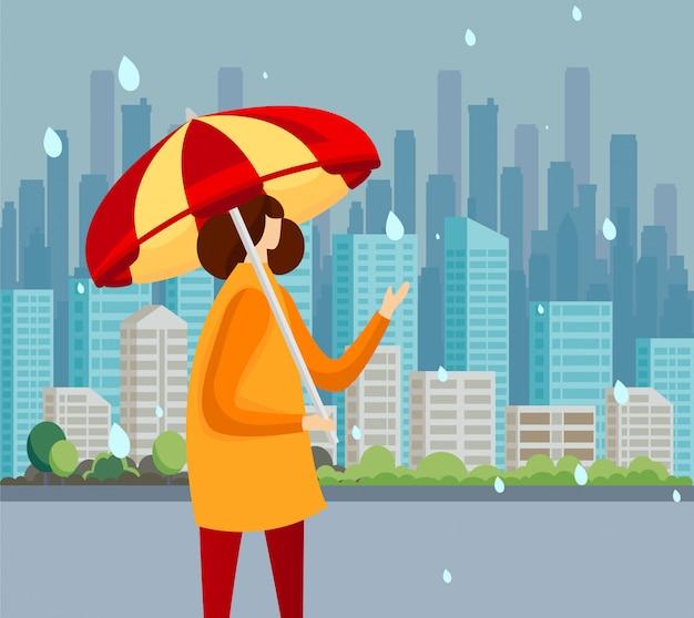Mujer joven en la capa que se coloca en las gotas de la captura de la lluvia.