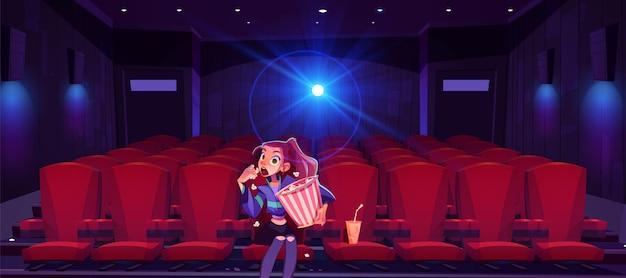 Mujer joven en el cine hipnotizado chica con cubo de palomitas de maíz en manos sentado solo en el cine