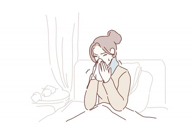 La mujer joven enferma cogió estornudos fríos en el tejido en casa.