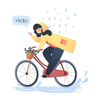 Mujer joven en un impermeable amarillo monta una bicicleta bajo la lluvia