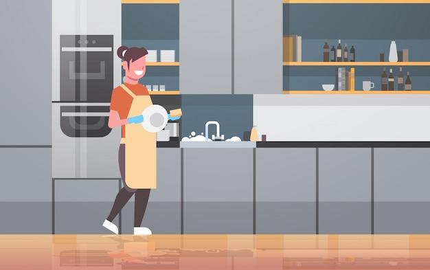 Mujer joven, lavar platos, sonriente, niña, limpiar, platos, moderno, cocina, interior, lavavajillas, concepto, ama de casa, quehacer doméstico