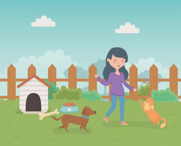 Mujer joven con lindas mascotas de perros y gatos en el campo