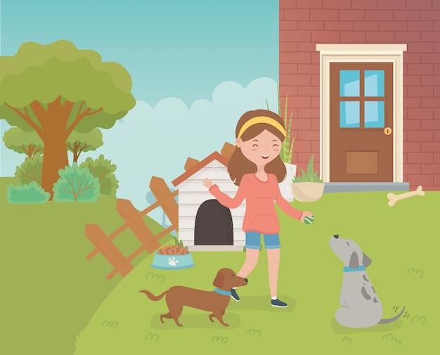 Mujer joven con mascotas de perros pequeños en el jardín de la casa