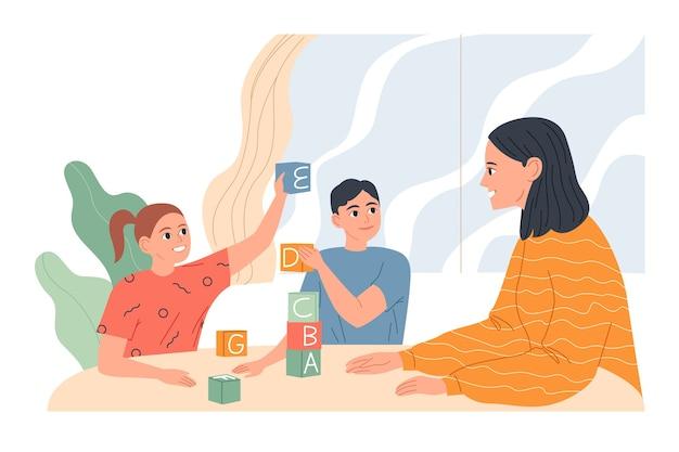 Mujer joven con niños en la mesa jugando y aprendiendo letras.