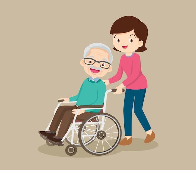 Mujer joven paseando con anciano en silla de ruedas