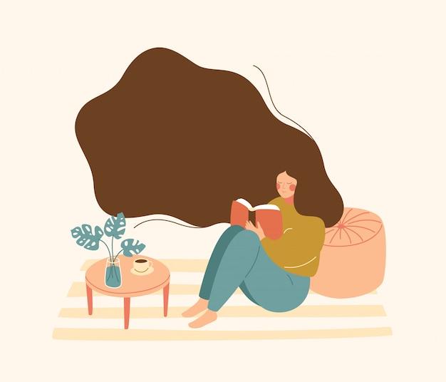 Mujer joven con pelo flotante se sienta en el piso y lee el libro.