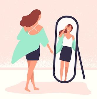 Mujer joven de pelo largo de pie delante del espejo y mirando la reflexión.