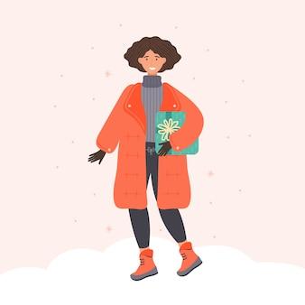 Mujer joven positiva en ropa de invierno con presente en compras de temporada festiva. personaje femenino de dibujos animados con caja de regalo.