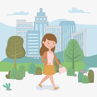 Mujer joven que camina con el bolso en el parque