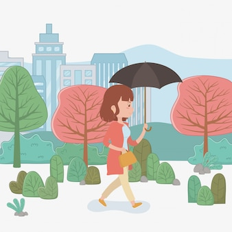 Mujer joven que camina con el paraguas en el parque