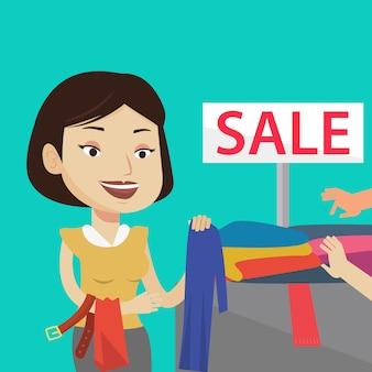 Mujer joven que elige la ropa en tienda en venta.