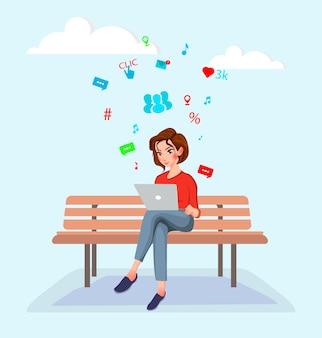 Mujer joven que se sienta en el banco y que trabaja con la computadora portátil.