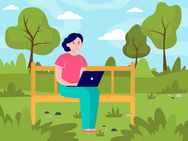 Mujer joven que trabaja con la computadora portátil en el parque