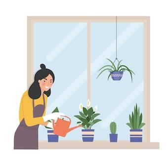 Mujer joven está regando las plantas de la casa