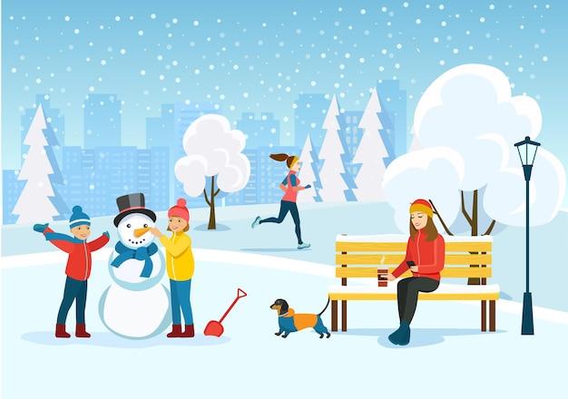 Mujer joven relajándose en el banco, mujer corriente y niños felices esculpe un muñeco de nieve en el parque.
