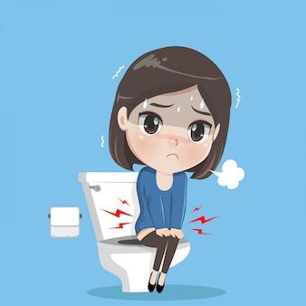 Mujer joven está sentada en el inodoro.
