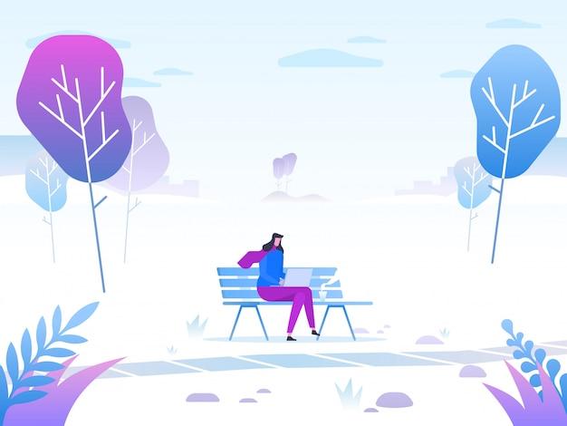Mujer joven sentada en el parque en el banco y trabajando con el portátil.