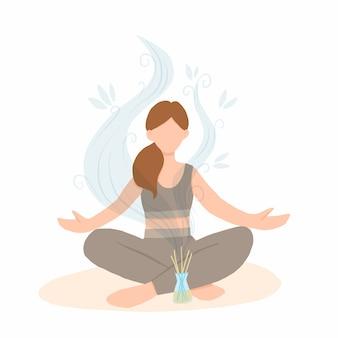 Mujer joven sentada en posición de loto con difusor de aroma.