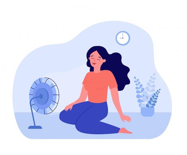 Mujer joven sentada en el suelo en el ventilador de refrigeración
