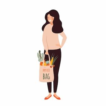 Mujer joven sostiene una bolsa de algodón ecológica llena de verduras frescas en sus manos .vector