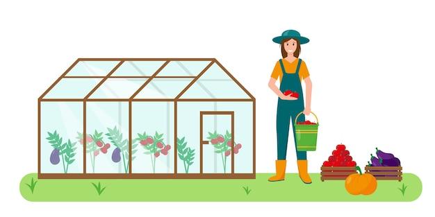 Mujer joven con verduras cerca de invernadero en el jardín