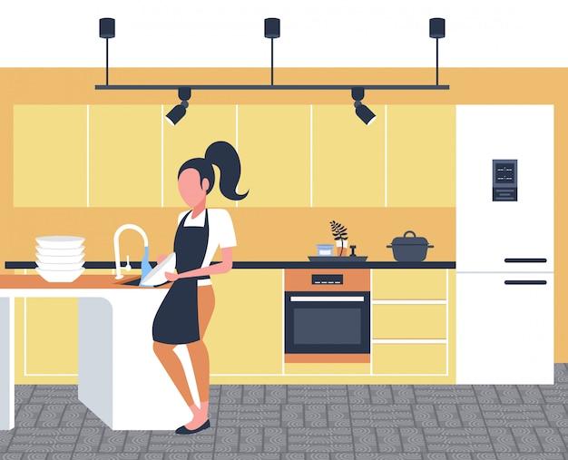 Mujer lavando platos ama de casa limpiando platos lavaplatos concepto chica en delantal haciendo tareas domésticas cocina moderna interior horizontal longitud completa
